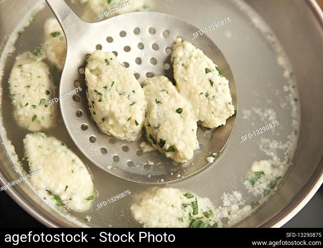 Cooked quark dumplings being removed from a pot