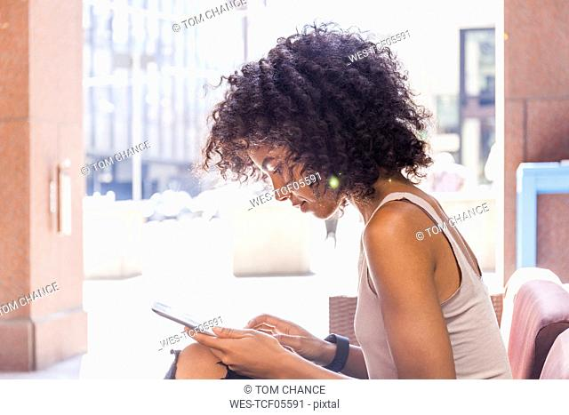 Young woman with curly hair sitting at sidewalk cafe using digital tablet