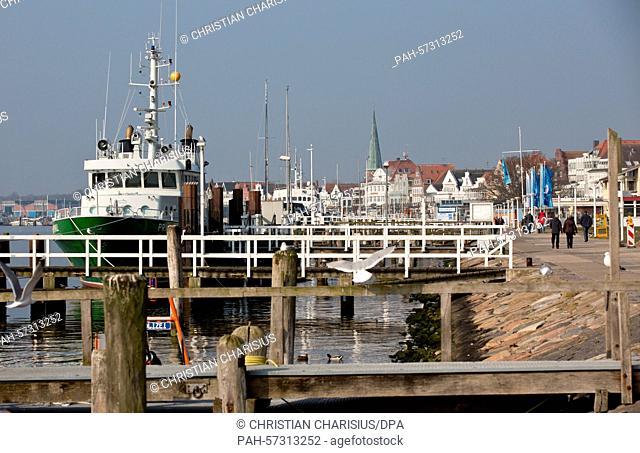 Pedestrians walk along the Trave Promenade in Luebeck-Travemuende, Germany, 10 April 2015. The DOSB selection panel and the city of Hamburg continue with their...