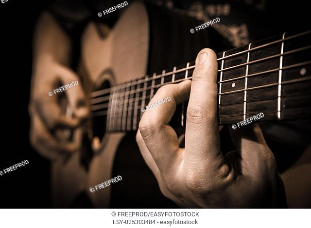 Close up of hands on the strings of a guitar, France