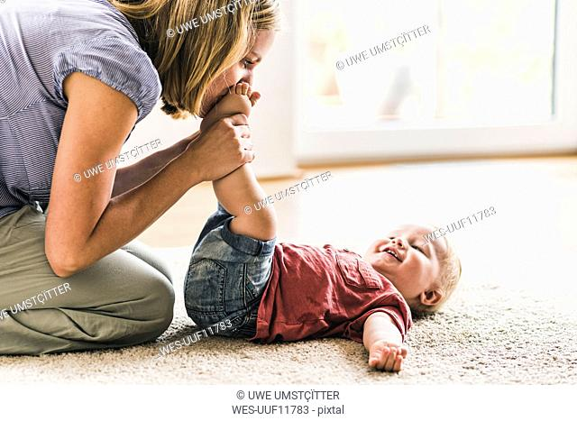 Mother playing with son at home