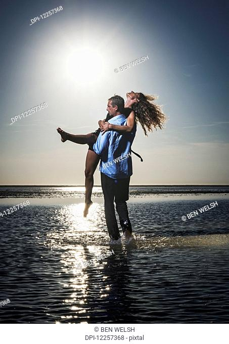 A man holds a woman in the shallow water along the coast looking out at the ocean; Tarifa, Cadiz, Andalusia, Spain