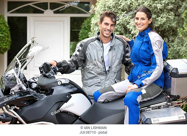 Portrait of smiling couple on motorcycle in driveway
