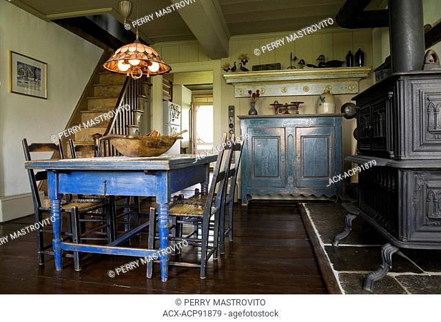 Old blue painted wooden antique dining table and chairs with black cast-iron wood burning oven in the original kitchen and dining room inside an old (1785)...