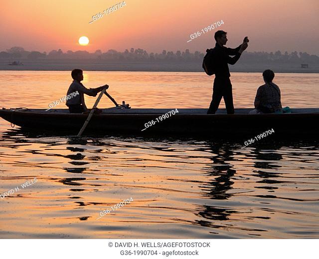 People traveling on boat during sunrise, Varanasi, Uttar Pradesh, India