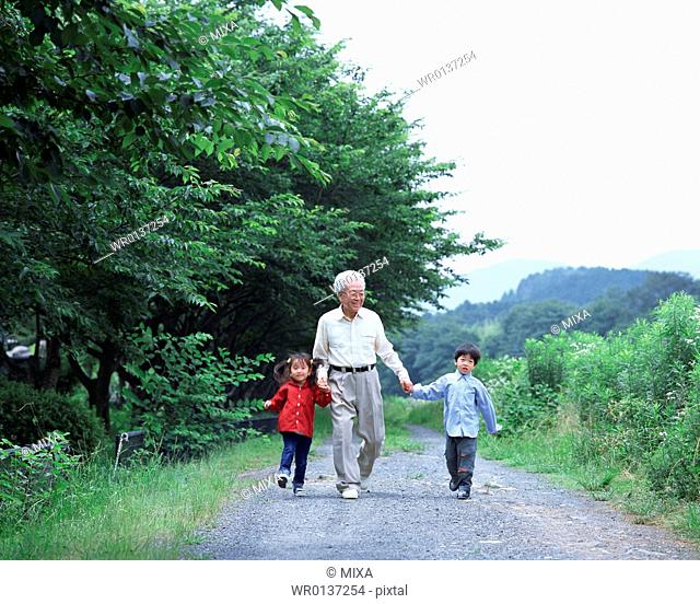 A grand father walking with grand children