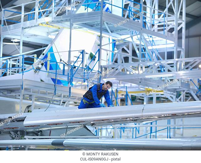 Engineer working on aircraft wing in aircraft maintenance factory
