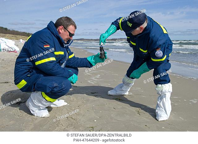 Members of staff of the 'Technische Hilfswerk, THW', the German federal Agency for Technical Relief, collect samples following the cleaning of the beach from...