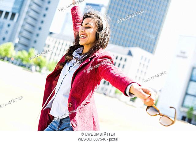 Happy young woman with headphones moving outdoors