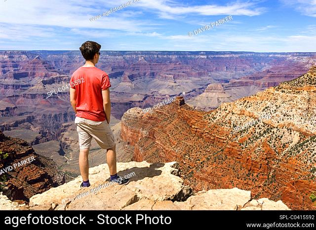 Young man surveying the Grand Canyon from one of the many overlook points on the South Rim. Behind him are the red-rocks of the North Rim