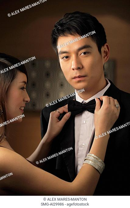 Young man getting his bow tie straightened by a woman