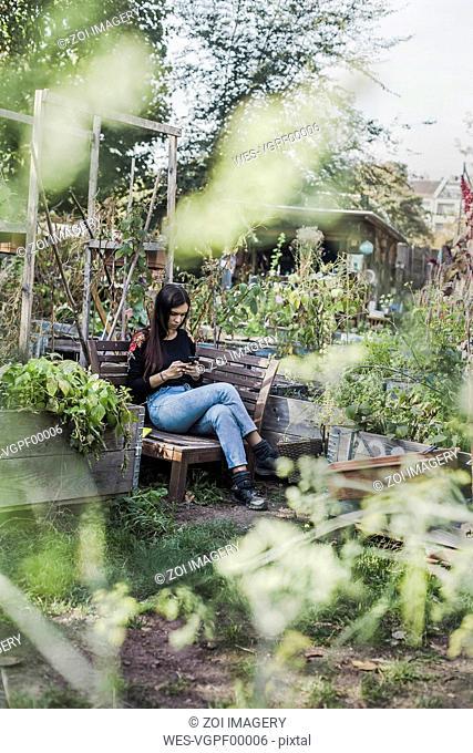 Woman using smartphone in urban garden