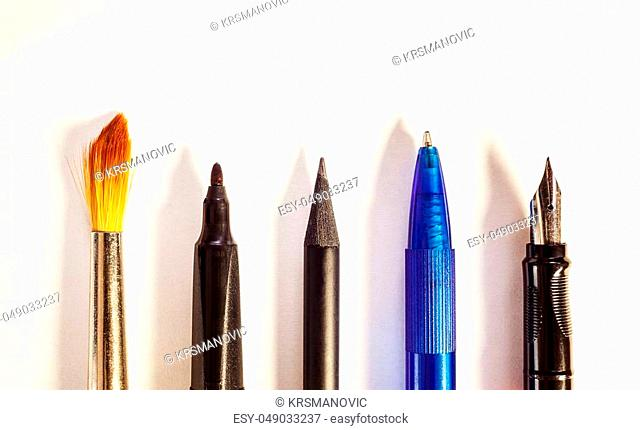 Various tools for writing or painting, conceptual composition on white paper