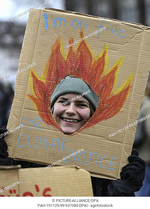 "29 November 2019, Baden-Wuerttemberg, Freiburg: At the action day of """"Fridays for Future"""" a schoolgirl holds a poster with the inscription """"I'm on fire for..."