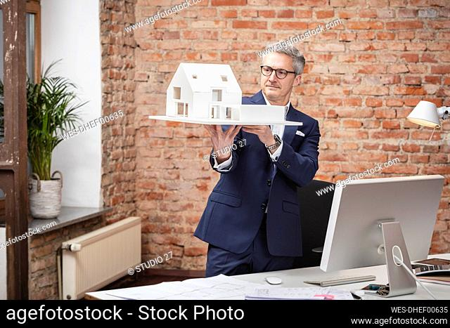 Mature male architect examining model house while standing by desk in office