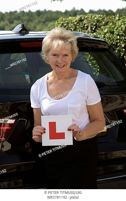Elderly woman driver with an self adhesive L plate
