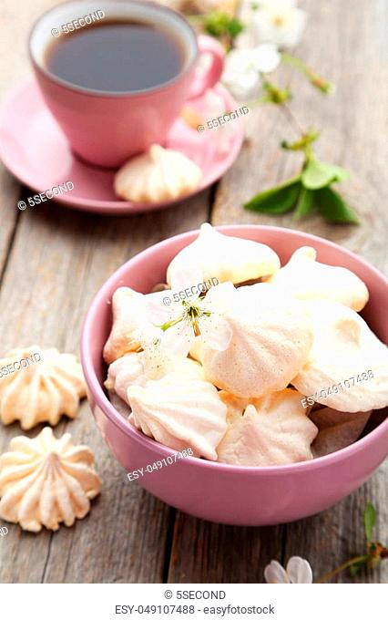 French meringue cookies in bowl on grey wooden background