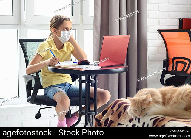 A sick girl in self-isolation sits at a table and does homework online