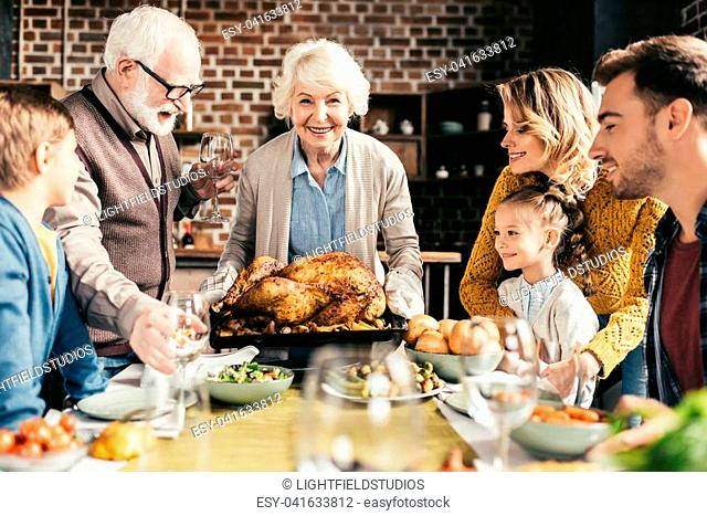 happy family looking at delicious thanksgiving turkey in hands of grandmother