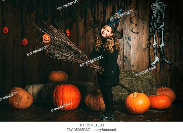 Portrait of a cute little child girl in a witch costume with magic broom. Happy Halloween!