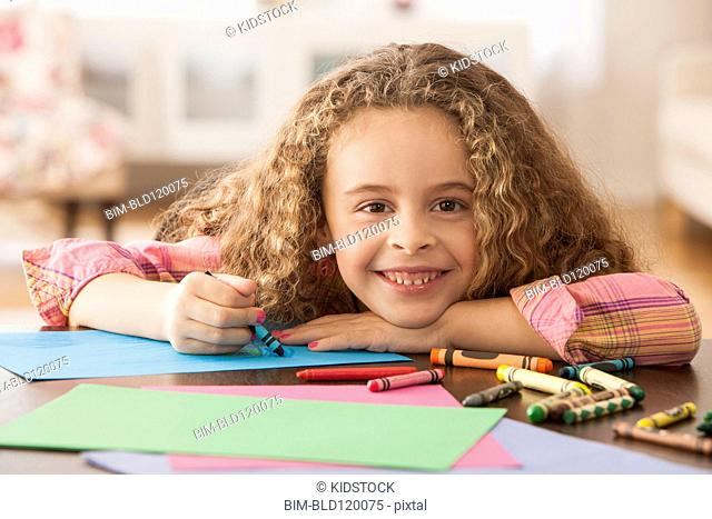 Hispanic girl drawing at table