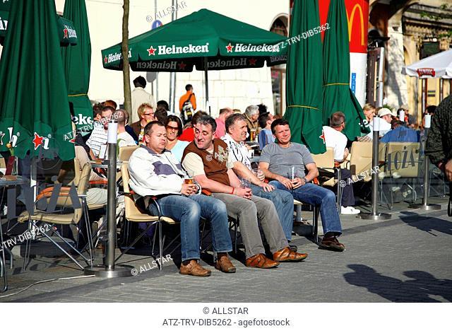 TOURIST ENJOY A DRINK IN STREET CAFE; RYNEK GLOWNY MARKET SQUARE, KRAKOW, POLAND; 29/04/2007