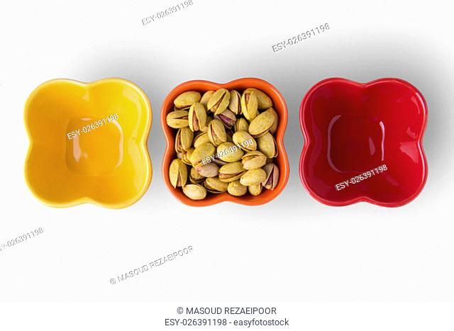 Pistachio Nuts on Colorful Bowls Isolated on White Background, Cllipping Path Included