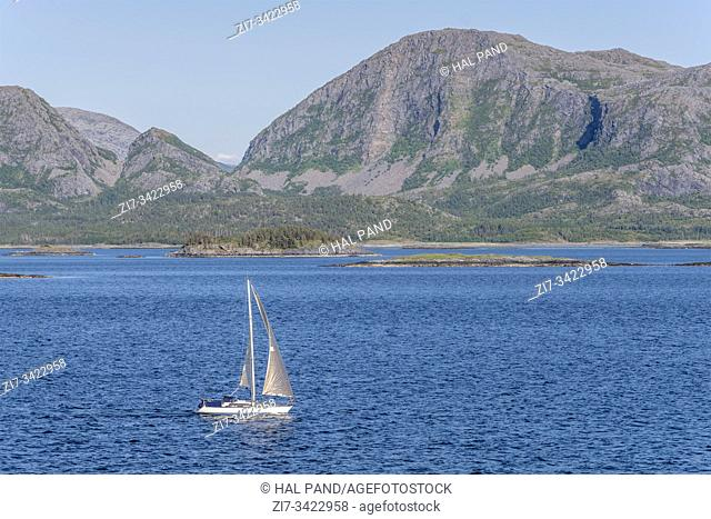 fjord landscape with sailboat sailing in front of cliffs and rocky steep slpes, shot under bright summer light at somnesoya island, Norway