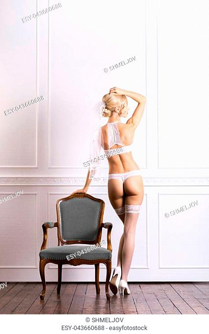 Sexy and beautiful young girl in bridal lingerie over retro background. Fashion, glamour, concept