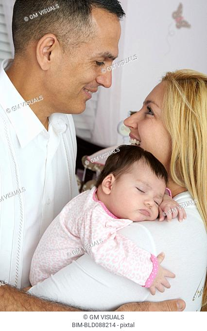 Hispanic parents holding baby daughter