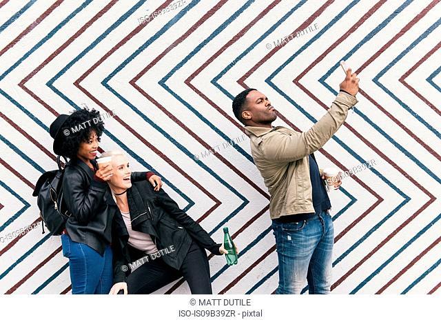 Friends taking selfie in front of zig zag pattern wall
