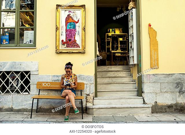 A woman sits on a bench outside a yellow building; Athens, Greece