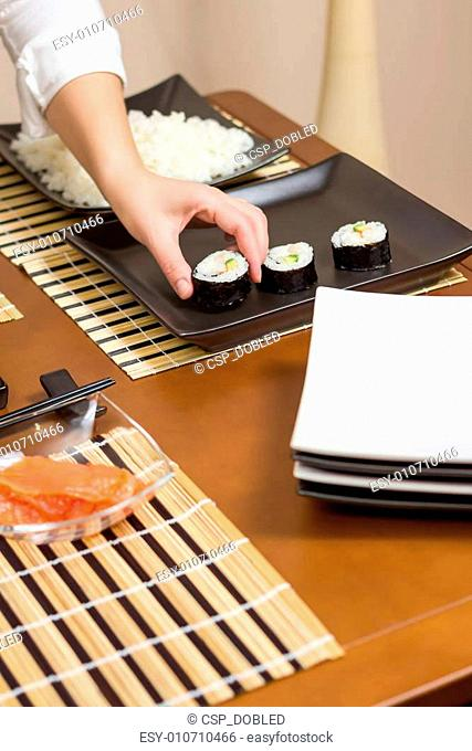Woman chef placing japanese sushi rolls on a tray