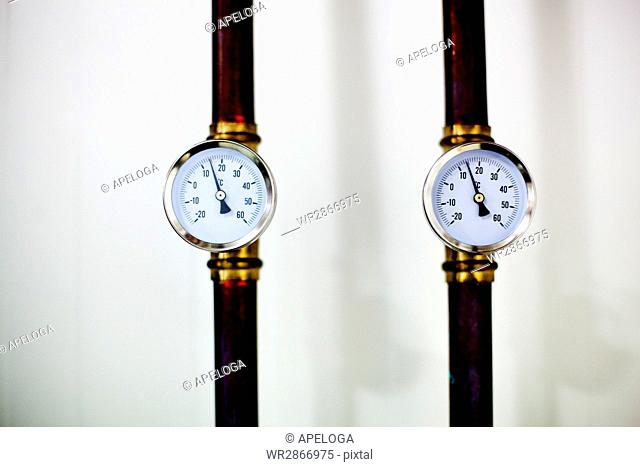 Directly above shot of pressure gauges on metal against white background