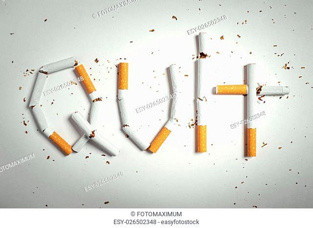Broken cigarettes arranged as a word quit - stop smoking concept