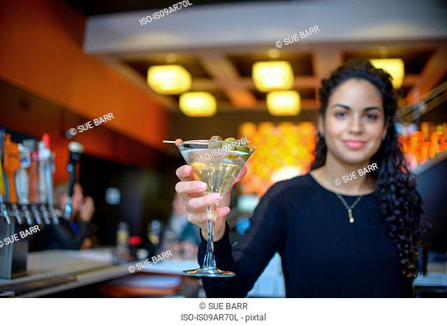 Young female bartender handing cocktail in cocktail bar