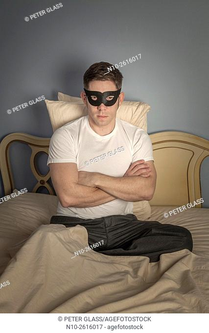 Young man, sitting on bed, wearing black mask