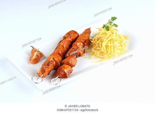 Red pepperd pork brochette with potato chips