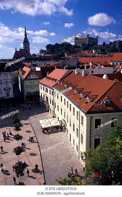 View over paved square and cafe, across red tiled rooftops of the Old Town towards Cathedral of St Martin and Bratislava Castle