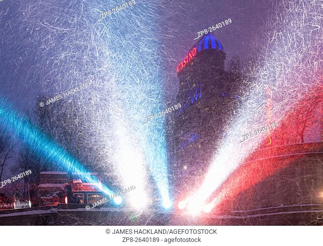 Colourful spotlights illuminating falling snow with Fallsview Casino in the background. Niagara Falls, District Municipakity of Niagara, Ontario, Canada