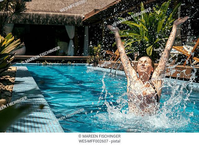 Brazil, Porto Seguro, woman splashing with water in the swimming pool
