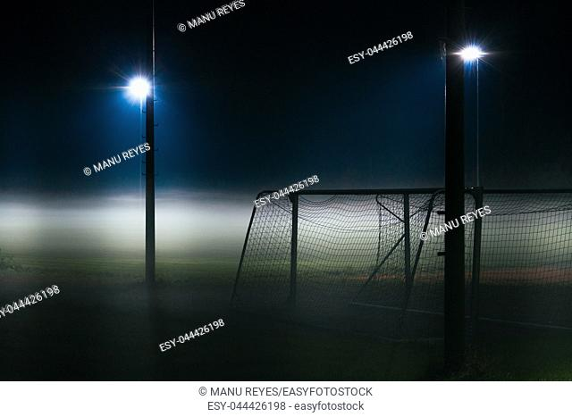 Lonely football field covered by fog at night only illuminated by spotlights. Baviera, Germany