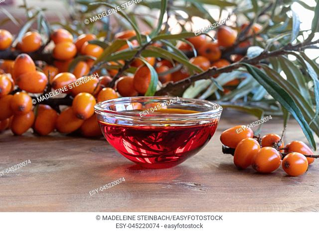 Sea buckthorn oil in a bowl with fresh berries