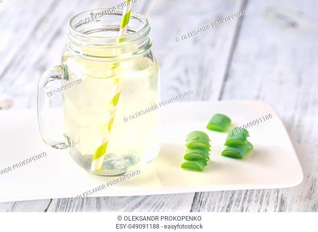 Aloe Vera drink in mason jar on the white wooden background