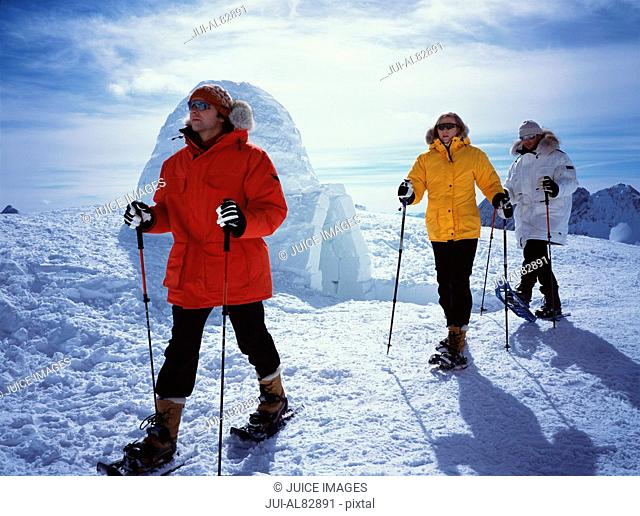Hikers on snowshoes near igloo
