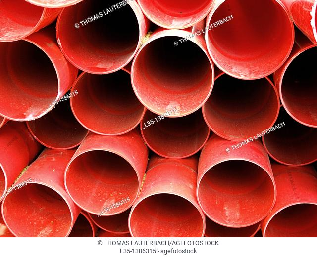 Many red plastic pipes stacked
