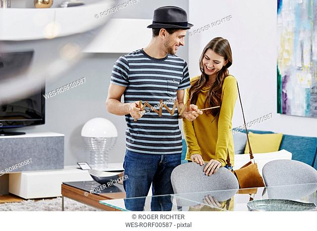 Couple in furniture store measuring dining table with pocket rule