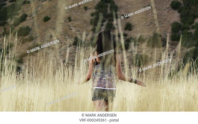 WS Rear view of teenage girl (16-17) walking through tall grass on field, South Fork, Utah, USA