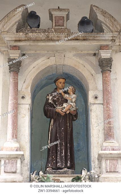 Pigeons by religious sculpture of monk with child, Venice, Italy