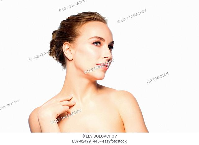 beauty, people and health concept - beautiful young woman touching her neck over white background